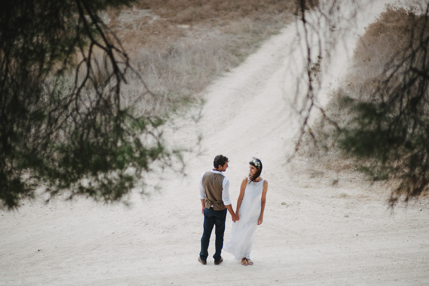 bride and groom standing in dirt road crossing