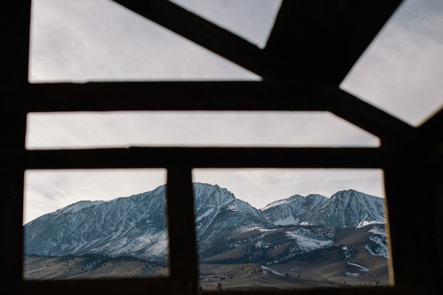 snowy mountains through cabin window