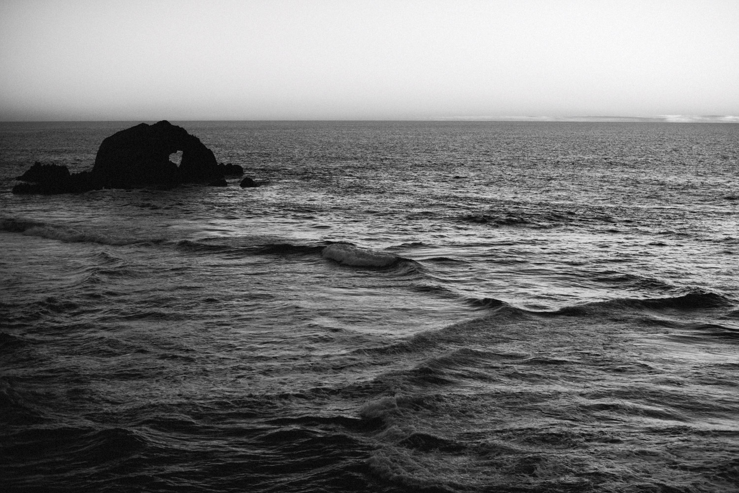 sunset over rock in black and white